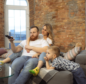 young couple with little boy watching tv at home
